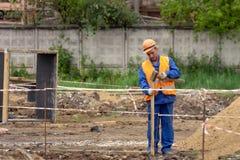 Erbauer stellt einen Zaun an der Baustelle her stockfotos