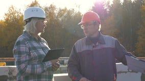 Erbauer und Vorarbeiter im Sturzhelm und Schutzbrillen stehen auf dem Bau gegen Sonne stock footage