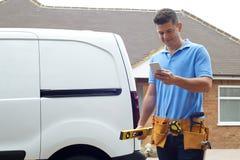 Erbauer With Van Texting On Mobile Phone außerhalb des Hauses Lizenzfreie Stockbilder