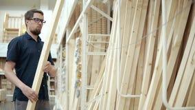 Erbauer wählt hölzerne Bretter in einem Baumaterialspeicher vor stock video footage