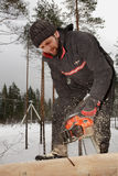 Erbauerarbeitskraft bei den hölzernen Arbeiten, die hölzernes Bauholz mit Kettensäge schneiden Stockfotos