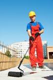 Erbauerarbeitskraft bei der Dachisolierungsarbeit Stockbilder