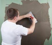 Erbauerarbeitskraft an der Wand des Hausbaus Stockfotos
