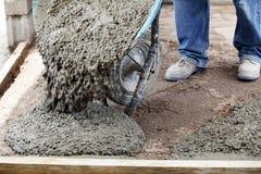 Erbauerarbeitskraft, die eine Schubkarre mit Zement entlädt Stockfotos