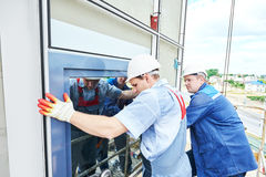 Erbauerarbeitskraft, die Glasfenster auf Fassade installiert stockbild