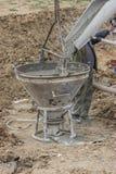 Erbauerarbeitskraft, die konkreten Trichter füllt Lizenzfreies Stockfoto