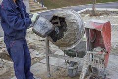 Erbauerarbeitskraft, die Wasser in einen Betonmischer 2 einsetzt Stockbild