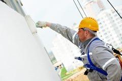Erbauerarbeitskraft-Malereifassade des Gebäudes mit Rolle stockfoto