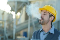 Erbauerarbeitskraft mit Zigarettenrauchbruch lizenzfreie stockfotografie
