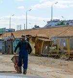 Erbauerarbeitskraft trägt eine Schubkarre Stockfotografie