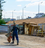 Erbauerarbeitskraft trägt eine Schubkarre Lizenzfreies Stockfoto