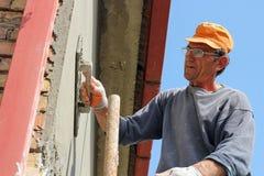 Erbauerarbeitskraft am Vergipsen der Fassadenarbeit stockbilder