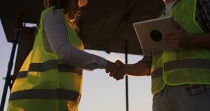Erbauermann mit einer Tablette und ein Fraueninspektor in den weißen Sturzhelmen rütteln Hände bei dem Sonnenuntergang, der auf d stock footage