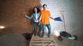 Erbauermann und das Mädchen mit dem Werkzeug Führen Sie Reparaturen im Haus durch Tanzen Sie und freuen Sie sich stock video