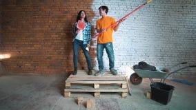 Erbauermann und das Mädchen mit dem Werkzeug Führen Sie Reparaturen im Haus durch Tanzen Sie und freuen Sie sich stock footage