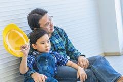 Erbauervater, der nahe bei seinem Sohn f?r Konzept der famili?ren Beziehung sitzt stockfotografie