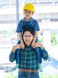 Erbauervater, der seinen Sohn auf seinem Hals für Vatersohn-Erfolgskonzept trägt stockfotografie