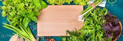 Erbe differenti insalata, aneto, prezzemolo, coriandolo su un fondo di legno Posto per testo Immagini Stock