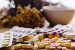 Erbe e compresse medicinali in mortaio con il pestello Fotografie Stock