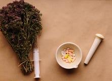 Erbe e compresse medicinali sulla tavola immagine stock libera da diritti