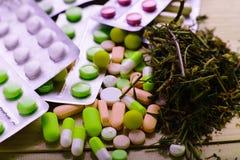 Erbe e compresse medicinali sulla tavola Immagini Stock