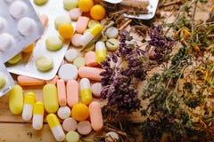 Erbe e compresse medicinali sulla tavola immagini stock libere da diritti