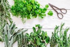 Erbe e pianta fresche di secchezza per l'alimento della spezia sulla vista superiore della cucina del fondo di legno bianco dello Immagini Stock