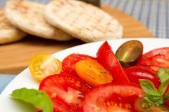 Erbe-tomatoe Salat mit flachen Broten Stockbild