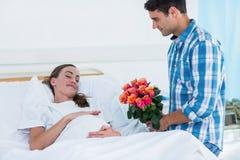Erbjudande blommor för man till gravida kvinnan i sjukhus Arkivbild