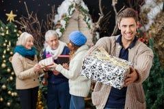 Erbjudande julklapp för lycklig man med familjen arkivfoto