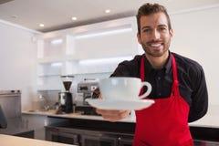 Erbjudande kopp kaffe för lycklig barista till kameran Arkivbilder