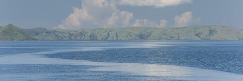 Erblassen Sie e-grün Hügel im Blaubelag, der in dem Ozean unter Cl steht Lizenzfreie Stockbilder