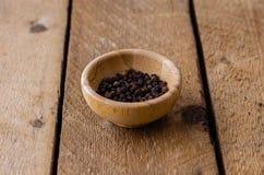 Erbsen des schwarzen Pfeffers in einer Bambusschüssel stockfotos
