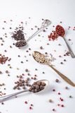 Erbsen des schwarzen, roten, weißen Pfeffers in den Metalllöffeln auf einem weißen Hintergrund Paprika, Paprika stockfotografie
