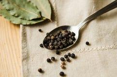 Erbsen-Lorbeerblatt des schwarzen Pfeffers ein Löffelserviettenholztisch Lizenzfreie Stockbilder