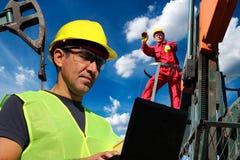 Erdöl-Ingenieure unter Verwendung des Laptops und die Entwicklung einer Ölquelle beaufsichtigen stockfoto