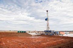 Erdölbohrung-Anlage und leerer Schlamm-Teich Stockfotos