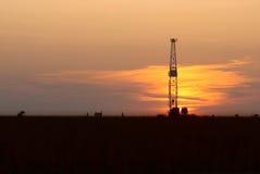 Erdölbohrung-Anlage und Sonnenuntergang Lizenzfreie Stockbilder
