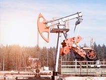 Erdölgewinnung, Ölquelle steht auf dem Feld unter dem Wald, blauer Himmel, die Gewinnung von Erdöl, industriell, Pumpe stockbilder