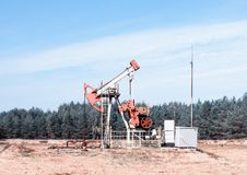 Erdölgewinnung, Ölquelle steht auf dem Feld unter dem Wald, blauer Himmel, Gewinnung von Erdöl lizenzfreie stockfotos