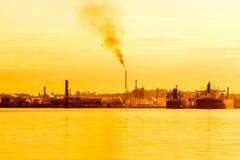 Erdölraffinerie bei dem Sonnenuntergang, der die Luft verunreinigt Stockbild