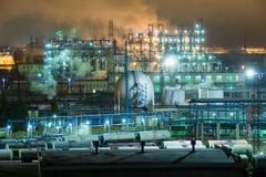 Erdölraffinerie mit Rohren und Destillationskomplexen nachts Lizenzfreie Stockbilder