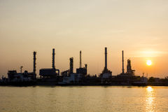 Erdölraffinerieansicht und -frachter mit Sonnenaufgang stockfotografie