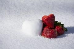 Erdbeer-und Schnee-Herz-Form auf weißem Schnee-Hintergrund stockfoto