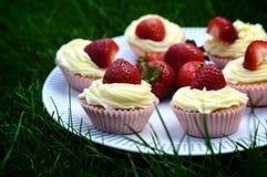 Erdbeer-und Vanille-kleine Kuchen auf Gras Stockbilder