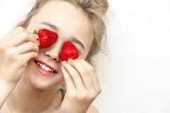 Erdbeeraugen Die sch?ne junge Frau, die Erdbeeren in den Augen h?lt, m?gen Ferngl?ser stockbilder