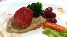 Erdbeerbrokkolitraube auf Hühnersteak Lizenzfreies Stockbild