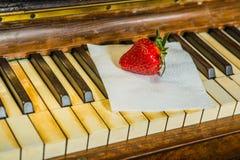 Erdbeere auf den Schlüsseln des Klaviers lizenzfreies stockbild
