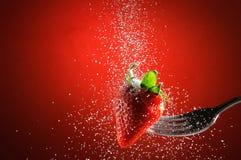 Erdbeere auf einem Gabel durchbohrten fallenden Zucker stockfoto
