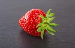 Erdbeere auf einem schwarzen Stein ist großer einer Lizenzfreie Stockfotos